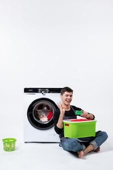 Vista frontal de um jovem homem esperando até o fim da lavagem das roupas na parede branca