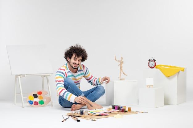 Vista frontal de um jovem homem fazendo desenhos com tintas na parede branca