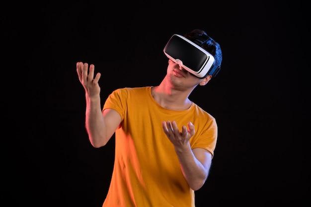 Vista frontal de um jovem homem jogando realidade virtual na parede escura
