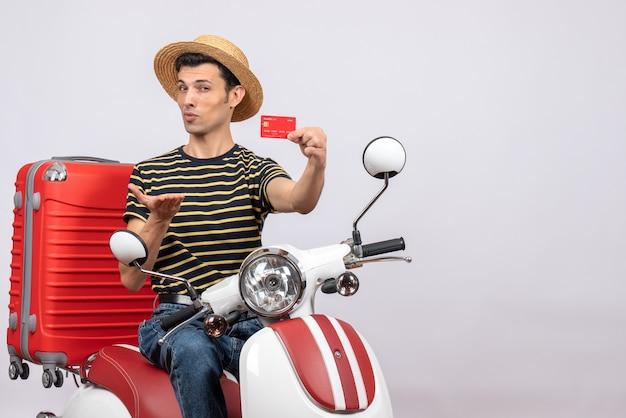 Vista frontal de um jovem inteligente com chapéu de palha na motocicleta segurando o cartão de descontos