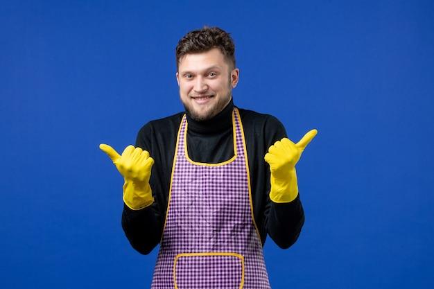 Vista frontal de um jovem macho fazendo sinal de pé na parede azul com o polegar