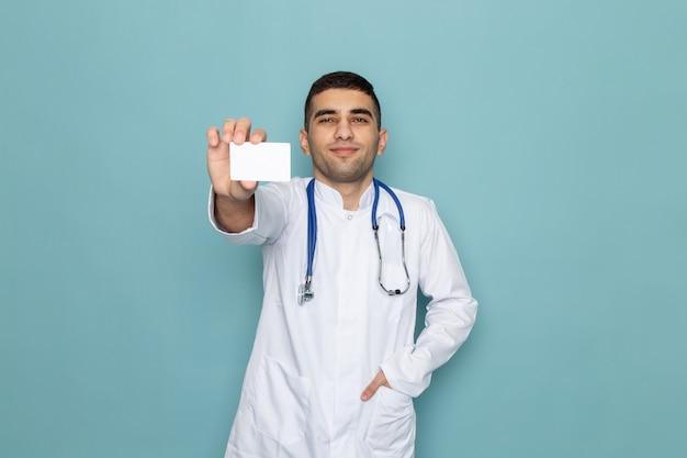 Vista frontal de um jovem médico de terno branco com estetoscópio azul segurando um cartão branco