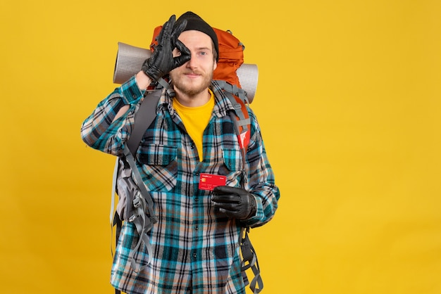 Vista frontal de um jovem mochileiro barbudo com chapéu preto segurando um cartão de crédito e fazendo sinal de ok