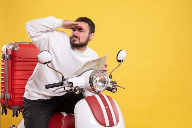 Vista frontal de um jovem nervoso concentrado sentado em uma motocicleta com uma mala segurando um mapa em fundo amarelo isolado