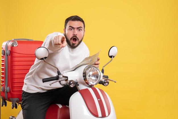 Vista frontal de um jovem nervoso sentado em uma motocicleta com uma mala segurando um mapa apontando para a frente em um fundo amarelo isolado