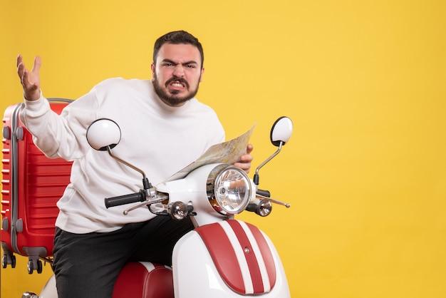 Vista frontal de um jovem nervoso sentado em uma motocicleta com uma mala segurando um mapa em fundo amarelo isolado
