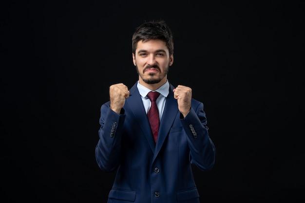 Vista frontal de um jovem orgulhoso e emocionado desfrutando de seu sucesso em uma parede escura isolada