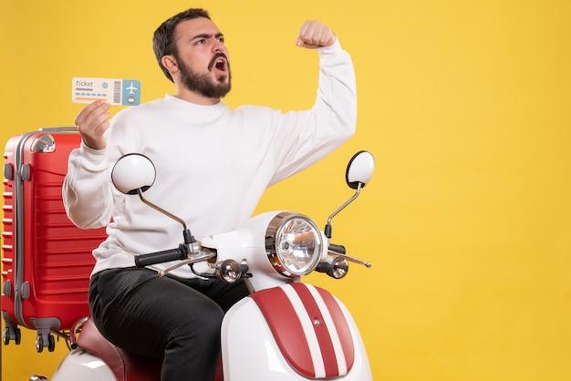 Vista frontal de um jovem orgulhoso viajando sentado em uma motocicleta com uma mala segurando o bilhete em fundo amarelo isolado