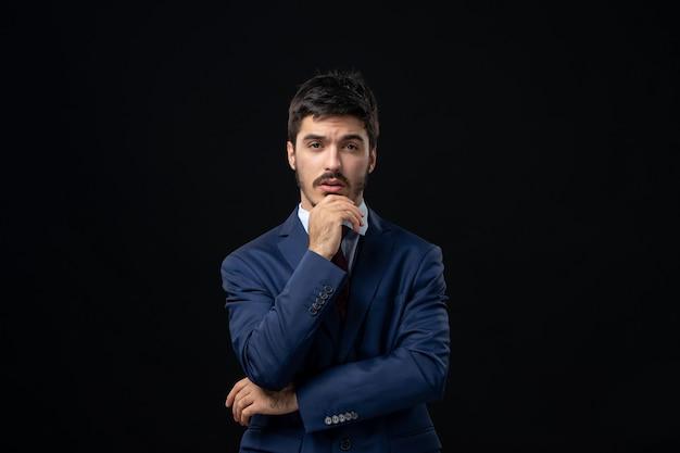 Vista frontal de um jovem pensativo barbudo posando em uma parede escura isolada