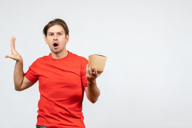 Vista frontal de um jovem preocupado com uma blusa vermelha segurando uma pequena caixa no fundo branco