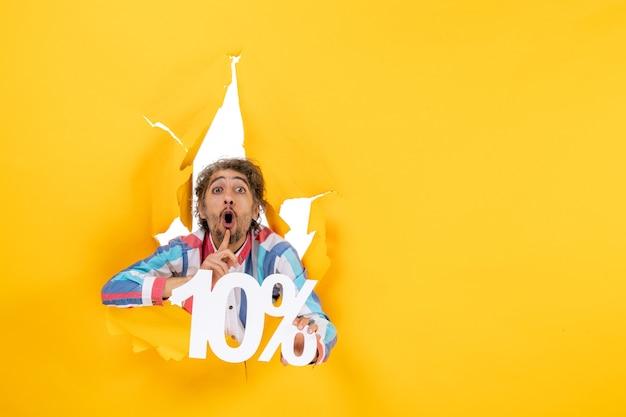 Vista frontal de um jovem preocupado segurando dez por cento fazendo gesto de silêncio em um buraco rasgado em papel amarelo