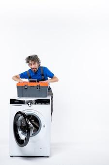 Vista frontal de um jovem reparador colocando as mãos em sua bolsa de ferramentas em pé atrás da máquina de lavar na parede branca