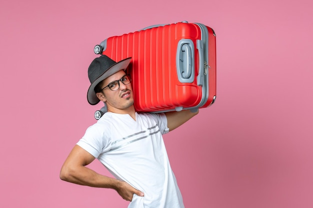 Vista frontal de um jovem saindo de férias segurando uma bolsa vermelha na parede rosa