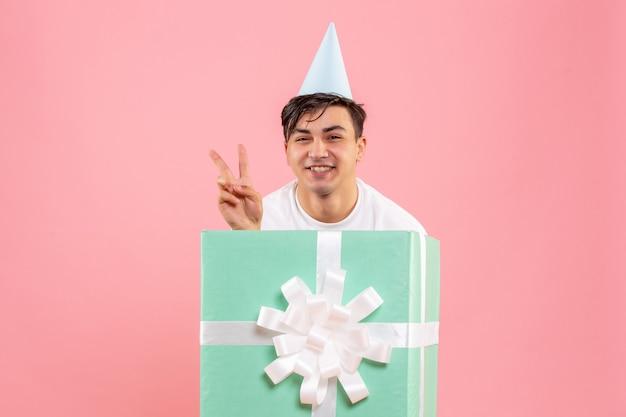 Vista frontal de um jovem se escondendo dentro de um presente sorrindo na parede rosa