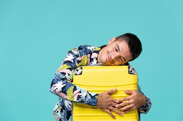 Vista frontal de um jovem se preparando para as férias com uma bolsa amarela, sentindo-se cansado na parede azul