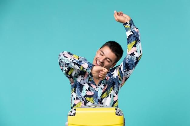Vista frontal de um jovem se preparando para as férias com uma bolsa dançando e sorrindo na parede azul