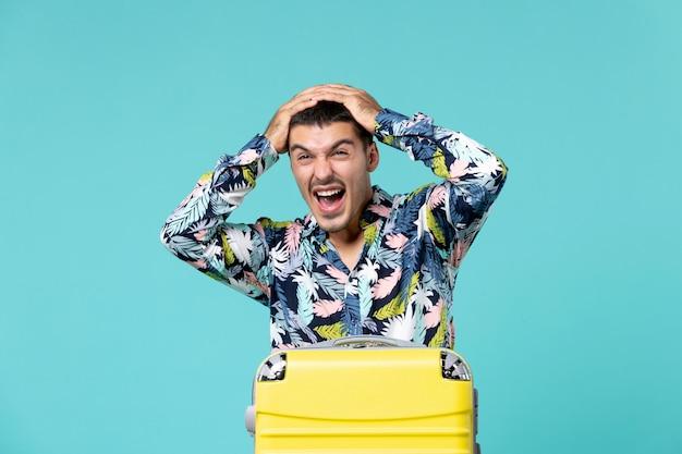 Vista frontal de um jovem se preparando para as férias com uma bolsa gritando na parede azul