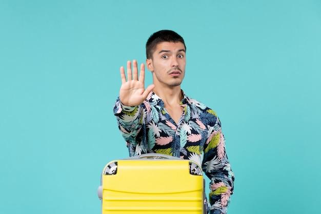 Vista frontal de um jovem se preparando para as férias e mostrando a placa de pare na parede azul