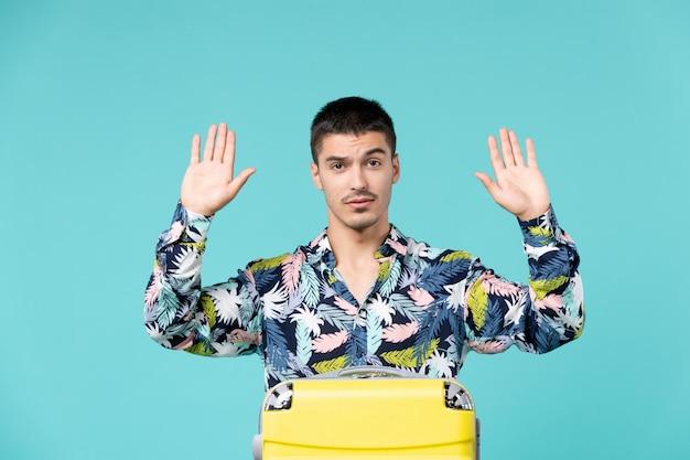 Vista frontal de um jovem se preparando para uma longa viagem na parede azul