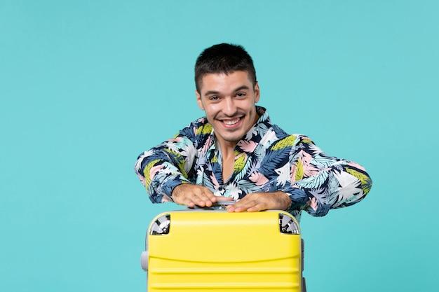 Vista frontal de um jovem se preparando para uma viagem com sua bolsa amarela na parede azul