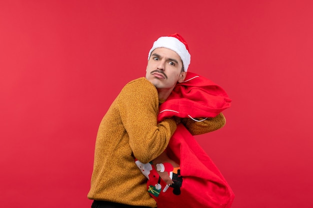 Vista frontal de um jovem segurando a sacola de presentes na parede vermelha
