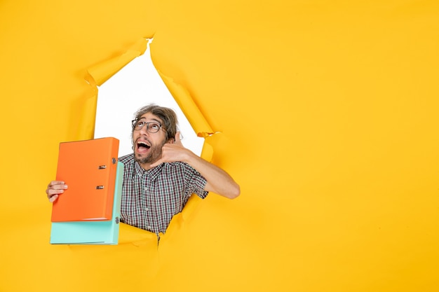 Vista frontal de um jovem segurando arquivos na parede amarela