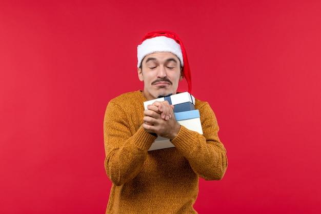 Vista frontal de um jovem segurando caixas de presentes na parede vermelha clara