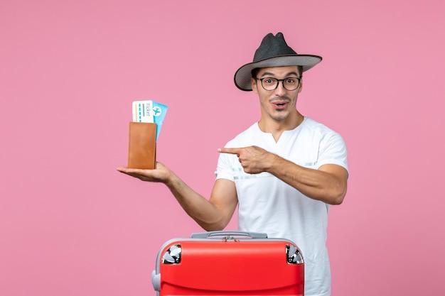 Vista frontal de um jovem segurando ingressos de férias dentro da carteira na parede rosa