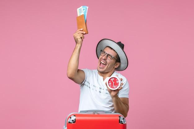 Vista frontal de um jovem segurando ingressos de férias e um relógio na parede rosa