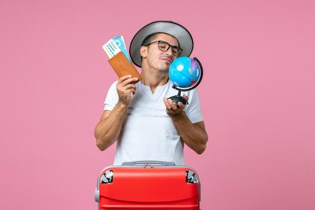 Vista frontal de um jovem segurando ingressos e um globo na parede rosa