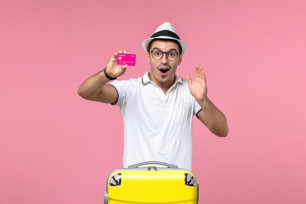 Vista frontal de um jovem segurando o cartão do banco na parede rosa