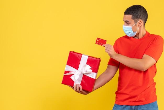 Vista frontal de um jovem segurando o presente e o cartão do banco na máscara em uma parede amarela