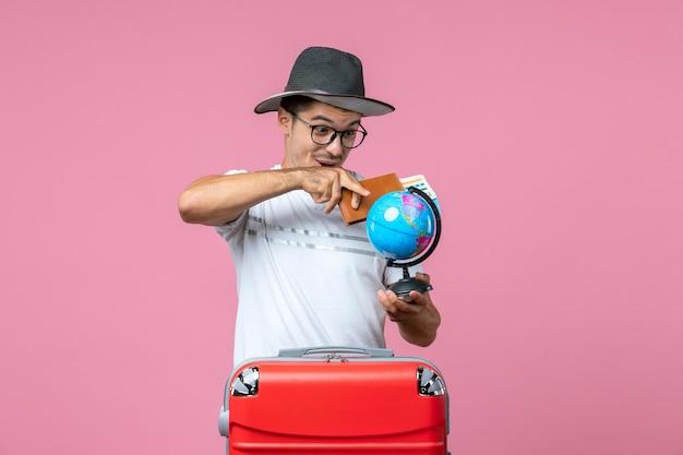 Vista frontal de um jovem segurando os bilhetes de férias e o globo na parede rosa
