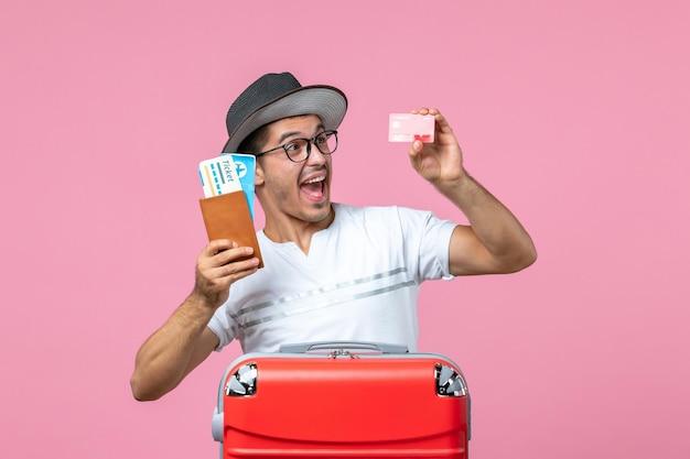 Vista frontal de um jovem segurando os ingressos e o cartão do banco na parede rosa