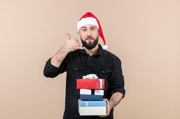 Vista frontal de um jovem segurando os presentes de natal na parede rosa