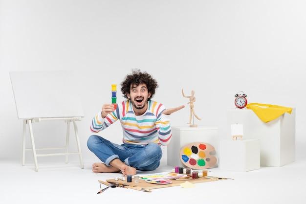 Vista frontal de um jovem segurando tintas para desenhar dentro de pequenas latas na parede branca