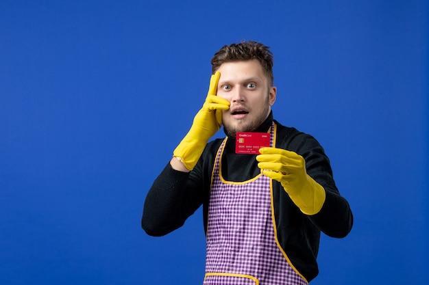 Vista frontal de um jovem segurando um cartão, colocando a mão em seu rosto na parede azul