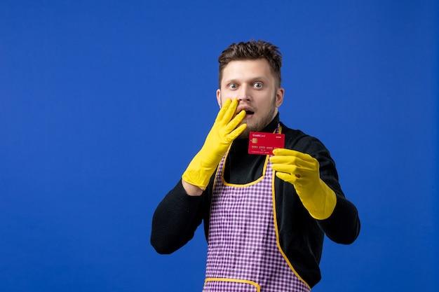 Vista frontal de um jovem segurando um cartão, colocando a mão no rosto na parede azul