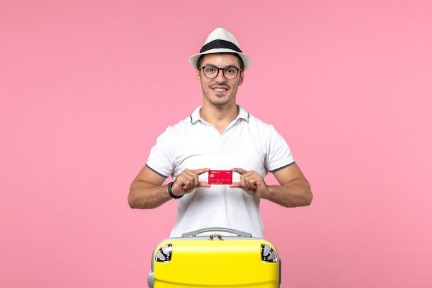 Vista frontal de um jovem segurando um cartão de banco vermelho nas férias de verão na parede rosa