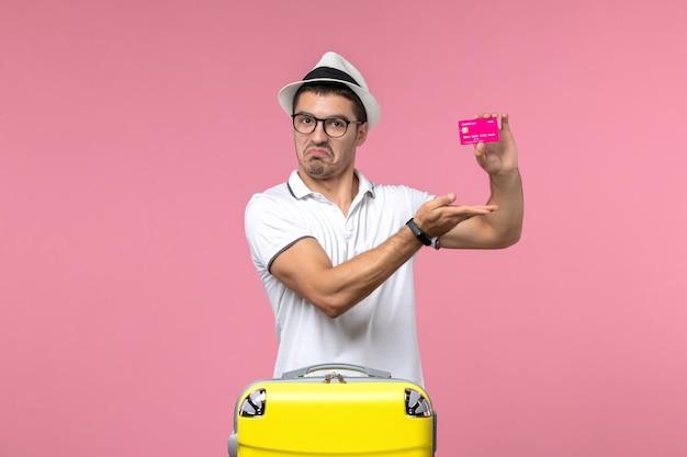 Vista frontal de um jovem segurando um cartão do banco de férias na parede rosa