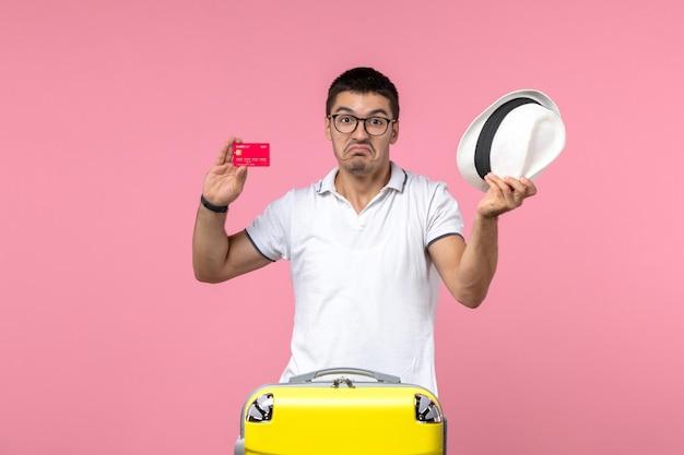 Vista frontal de um jovem segurando um cartão do banco e um chapéu na parede rosa