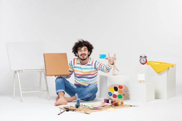 Vista frontal de um jovem segurando um cartão do banco e uma caixa de pizza na parede branca