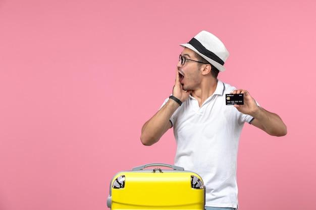 Vista frontal de um jovem segurando um cartão do banco nas férias de verão na parede rosa