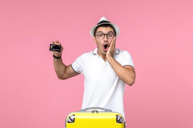 Vista frontal de um jovem segurando um cartão do banco preto com rosto em choque na parede rosa