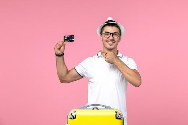 Vista frontal de um jovem segurando um cartão do banco preto na parede rosa claro