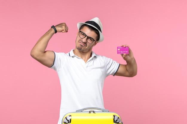 Vista frontal de um jovem segurando um cartão roxo do banco nas férias de verão na parede rosa