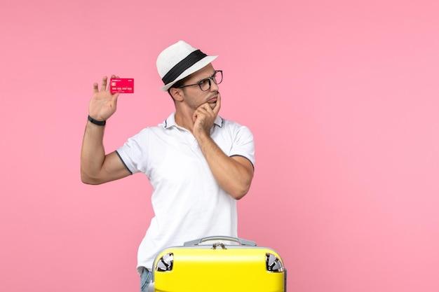 Vista frontal de um jovem segurando um cartão vermelho do banco na parede rosa claro