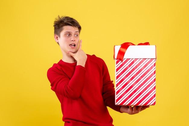 Vista frontal de um jovem segurando um grande presente de natal na parede amarela