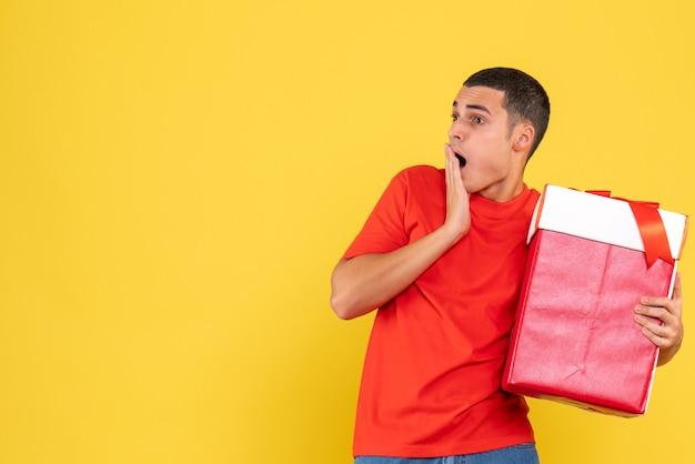 Vista frontal de um jovem segurando um presente de natal chocado na parede amarela
