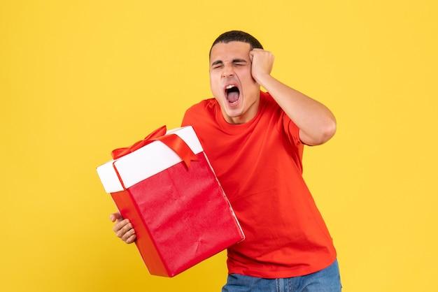 Vista frontal de um jovem segurando um presente de natal na parede amarela